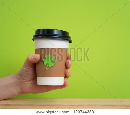 take away cup in a hand with cut and pasted green shamrock symbol on green background