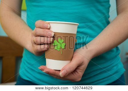 take away cup in a hand with cut and pasted green shamrock symbol