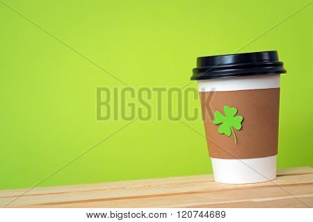 take away cup with cut and pasted green shamrock symbol on green background