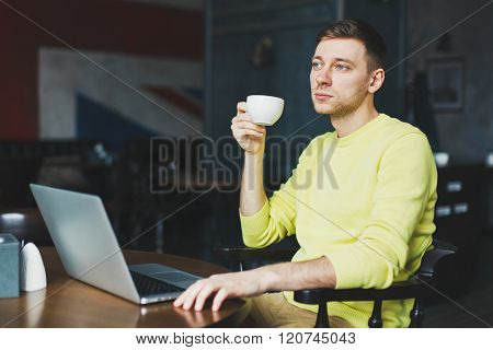 Adult man resting in a modern cafe after a hard day's work and drinking tea