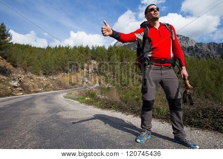Hitchhiking traveler try to stop car on the mountain road.