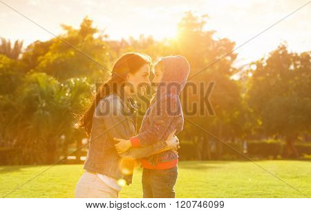 Side view on cheerful mother and daughter looking on each other, playing in the park in spring sunny day, happy family life