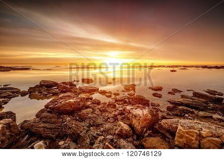 Beautiful sunset over sea, amazing peaceful beach landscape, picturesque view from stony seaside, beauty of nature