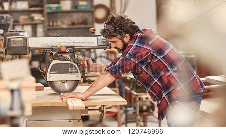 Craftsman using radial arm saw on some wood in workshop