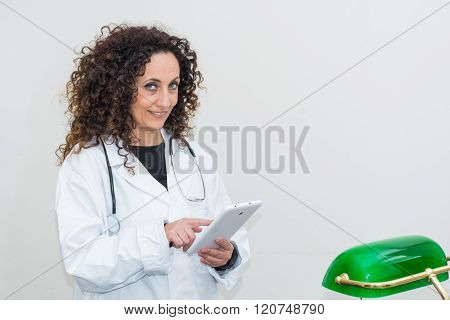 Doctor With Curly Hair And Blacks And With Green Eyes, Use A Tablet Of White Color.