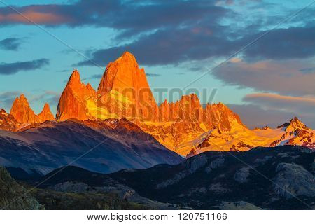 Blood-red sunset illuminates the top of impressive cliffs Fitz Roy. Fantastic Patagonia