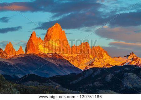 Blood-red sunset illuminates the top of impressive cliffs Fitz Roy. Fantastic Patagonia