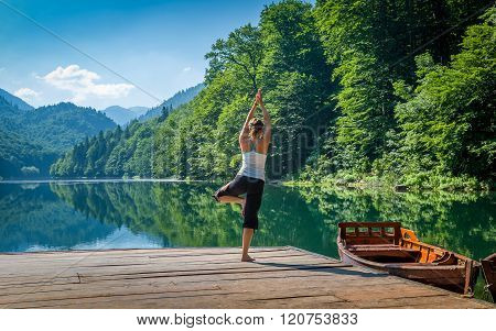 Yoga exercises at mountain forest lake.
