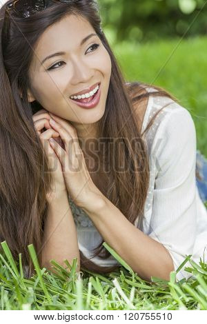 Outdoor portrait of a beautiful young happy smiling Chinese Asian young woman or girl