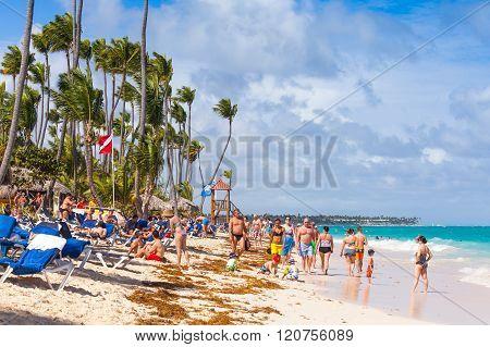 Tourists Walk Along Sandy Beach Of Punta Cana