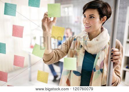 Woman designer make scheme on sticky notes on glass board at design studio