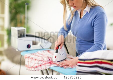 Nice woman patiently press clothes at home