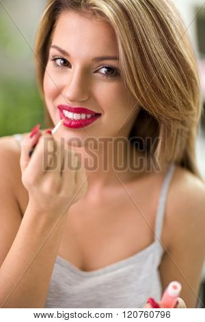Makeup young woman, cute cosmetics girl putting gloss on red lips
