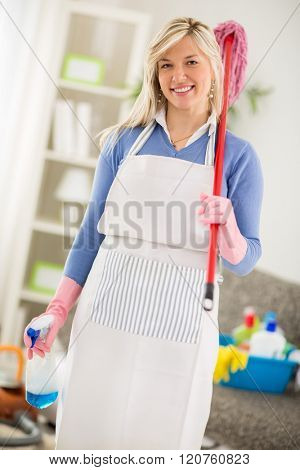 Cheerful hostess with equipment for cleaning house posing
