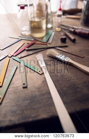 Paint brush, solvents and wood color samples on an old work bench.  Focus is on center  brush metal sleeve. Shallow depth of focus.