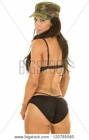 A woman with her back to the camera in her black bikini with a tattoo and camo hat on.