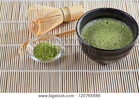 Green Matcha Tea Preparation Set On A Bamboo Table Mat