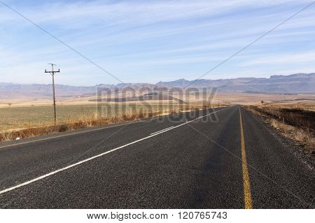 Straight Road Through Dry Landscape Stretching Into Moutains