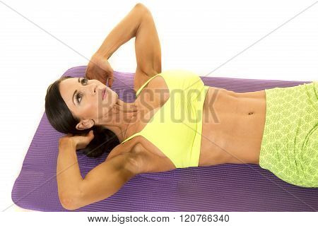 a woman laying on her fitness mat doing a crunch.
