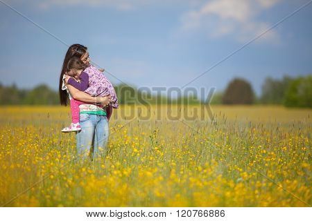 Mother With Her Daughter In A Field