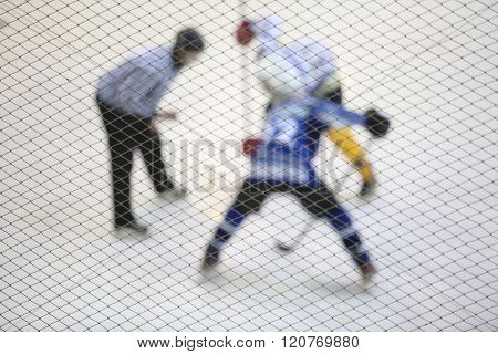 Two Ice Hockey Player And Referee Facing Off On Ice