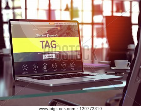 Tag on Laptop in Modern Workplace Background.