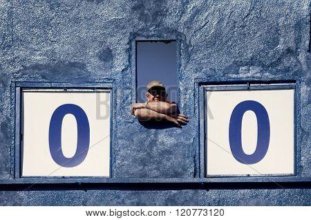 ALBA IULIA, ROMANIA- MAY 1, 2010: Unidentified man in charge with changing the score on an old blue score board watching a soccer game. Conceptual sport image.