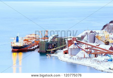 Industrial Container Cargo freight ship with working crane bridge in shipyard at Iron Ore Mine Factory Plant in Narvik Norway