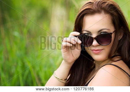 Beautiful woman looking over sunglasses