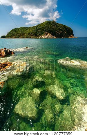 Green island in the sea with clear water.