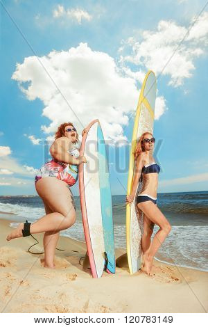 Beautiful young fat woman at the summer sea with the surfboard