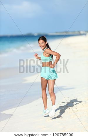 Happy healthy lifestyle woman runner jogging on white sand looking back smiling at camera. Asian fitness athlete young adult running on vacation beach showing off fit body and toned thighs and butt.