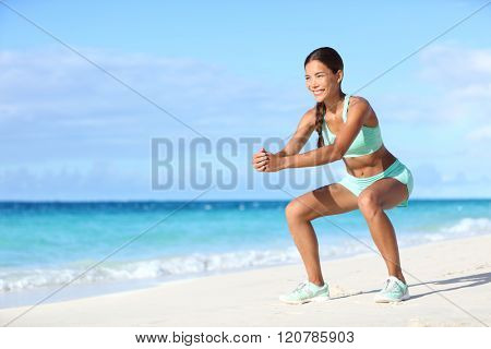 Fitness young woman working out core and glutes with bodyweight workout doing squat exercises on beach. Asian sporty girl squatting legs as part of an active and fit life.
