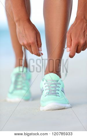 Sportswoman runner getting ready tying running shoes on beach. Fitness woman living a healthy and active life preparing for cardio training. Wellness and health concept.