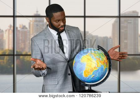 Sad black businessman with globe.