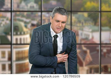 Mature businessman's heartache in office.