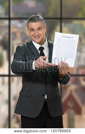 Smiling adult businessman shows contract.