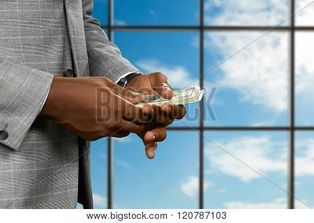 Businessman counts money near window.