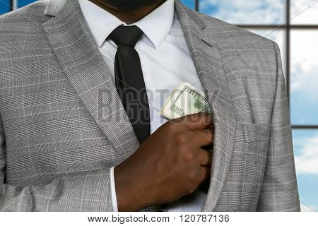 Black office worker hiding cash.