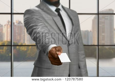 Darkskinned businessman with visit card.