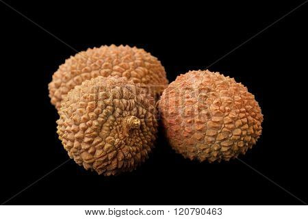 Three lychee fruits isolated on a black background