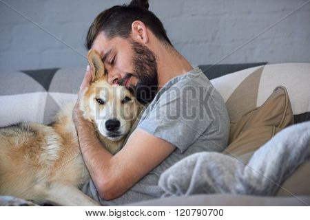 hipster man snuggling and hugging his dog, close friendship loving bond between owner and pet husky