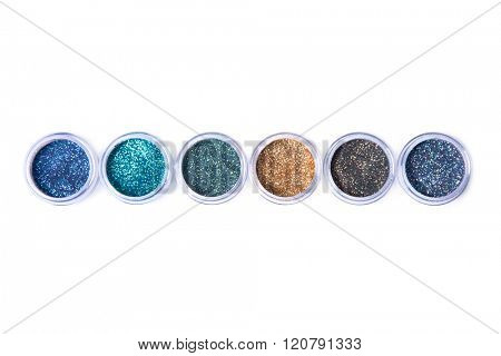 Row of bright glitters in transparent jars, top view isolated on white background