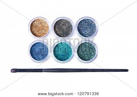 Top view of bright glitters in transparent jars, isolated on white background