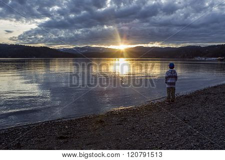 Boy Watches Sunset Over Lake.