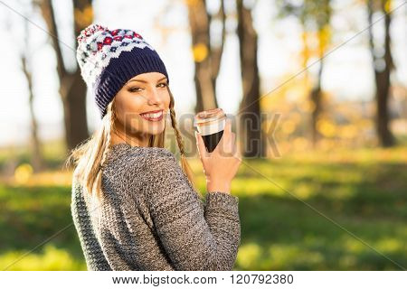 Modern Young Woman In Park With Takeaway Coffee