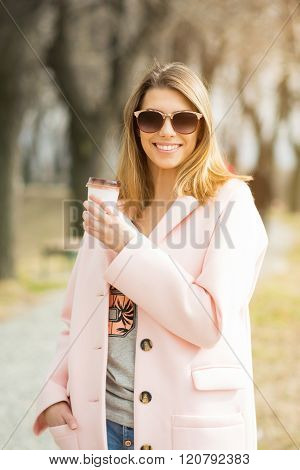 Young Woman In Pink Coat And Sunglasses With Takeaway Coffee