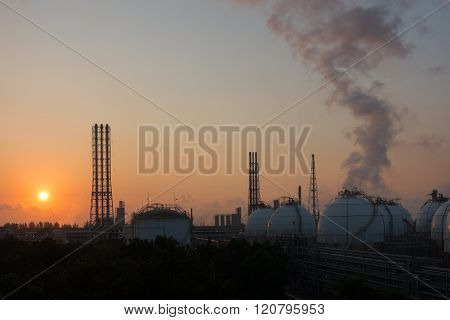 Storage tanks and Flare stacks with sunrising background