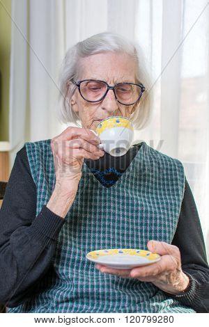 Grandma Having Cup Of Coffee Indoors