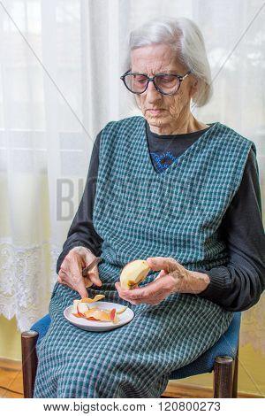Old Grandma Slicing And Peeling An Apple